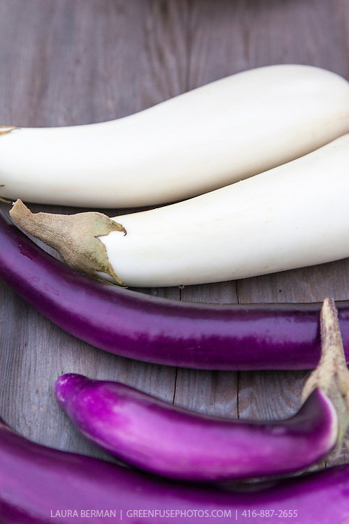 White  and purple Asian eggplants on a wood tabletop.