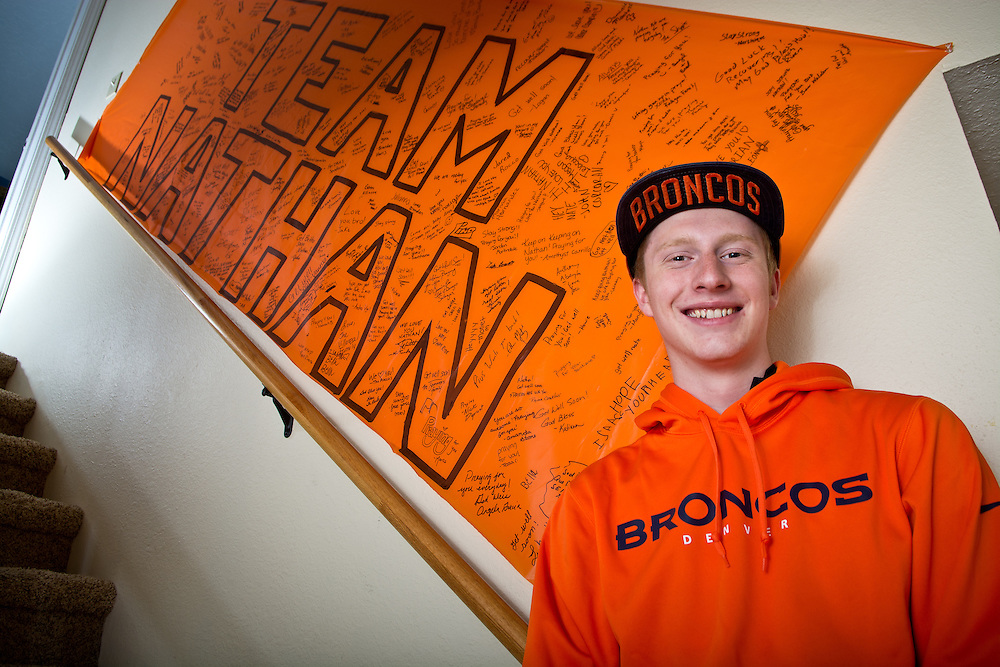 mkb080916c/metro/Marla Brose/080916<br /> Nathan Barkocy, 17, who lives in Albuquerque, N.M. right, stands under a poster signed with well wishes on the stairway just outside his bedroom door. Barkocy was  given Denver Bronco memorabilia as he recovered from his wreck in Denver. Barkocy was hit by a car and thrown from his bike during a training ride last January. Barkocy, who was in a coma for almost two week, has recovered and is getting ready to head back to school. (Marla Brose/Albuquerque Journal)