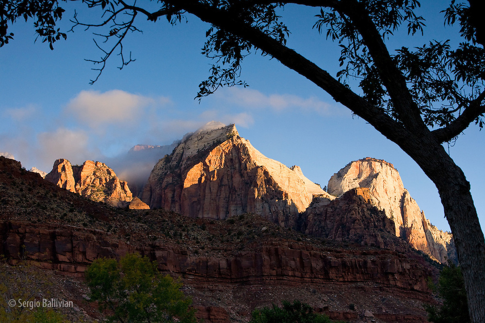 Clouds part to reveal the steep multicolored sandstone cliffs typical of Zion National Park near Springdale, Utah