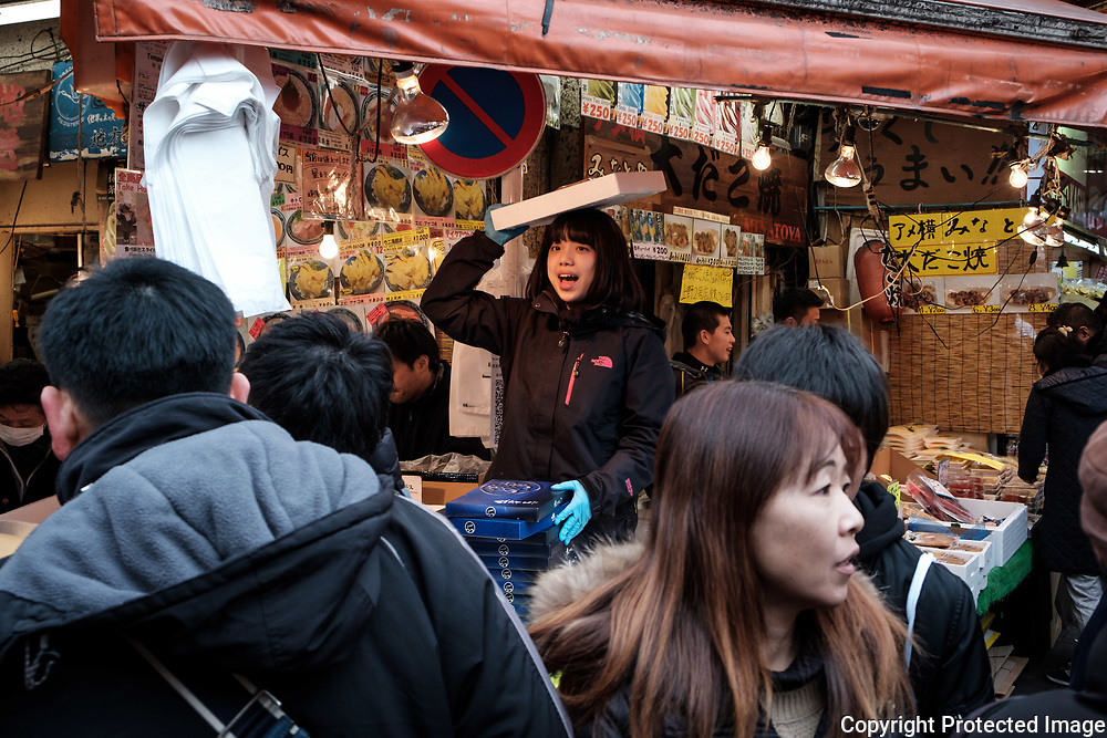 "A merchant present her products to customers at the Ameyoko market, Ueno in Tokyo Sunday, Dec. 31, 2017. Ameyoko market is crowded by shoppers who look for discounts on ingredients for ""osechi"" or Japanese traditional New Year dishes. 31/12/2017-Tokyo, JAPAN"