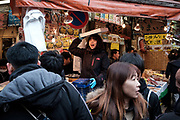 """A merchant present her products to customers at the Ameyoko market, Ueno in Tokyo Sunday, Dec. 31, 2017. Ameyoko market is crowded by shoppers who look for discounts on ingredients for """"osechi"""" or Japanese traditional New Year dishes. 31/12/2017-Tokyo, JAPAN"""