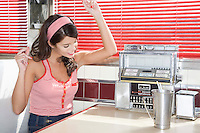 Young Woman Listening to Music in a Diner