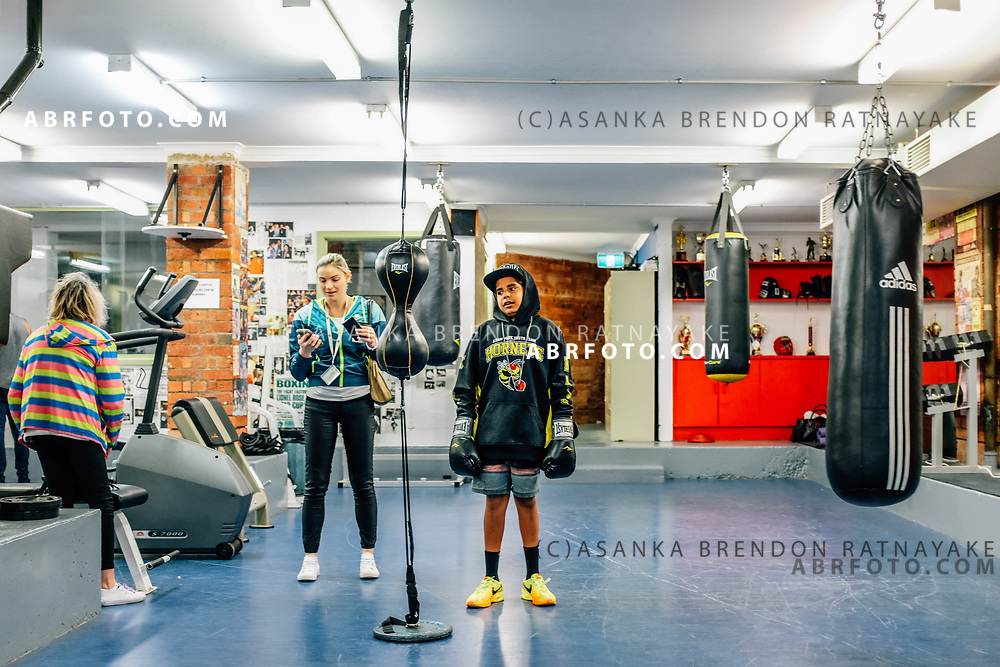 A young Aboriginal boy wearing boxing gloves inside the Aboriginal Youth Sport and Recreation centre on Gertrude Street in Melbourne, Australia, September 1, 2017. Asanka Brendon Ratnayake for the New York Times