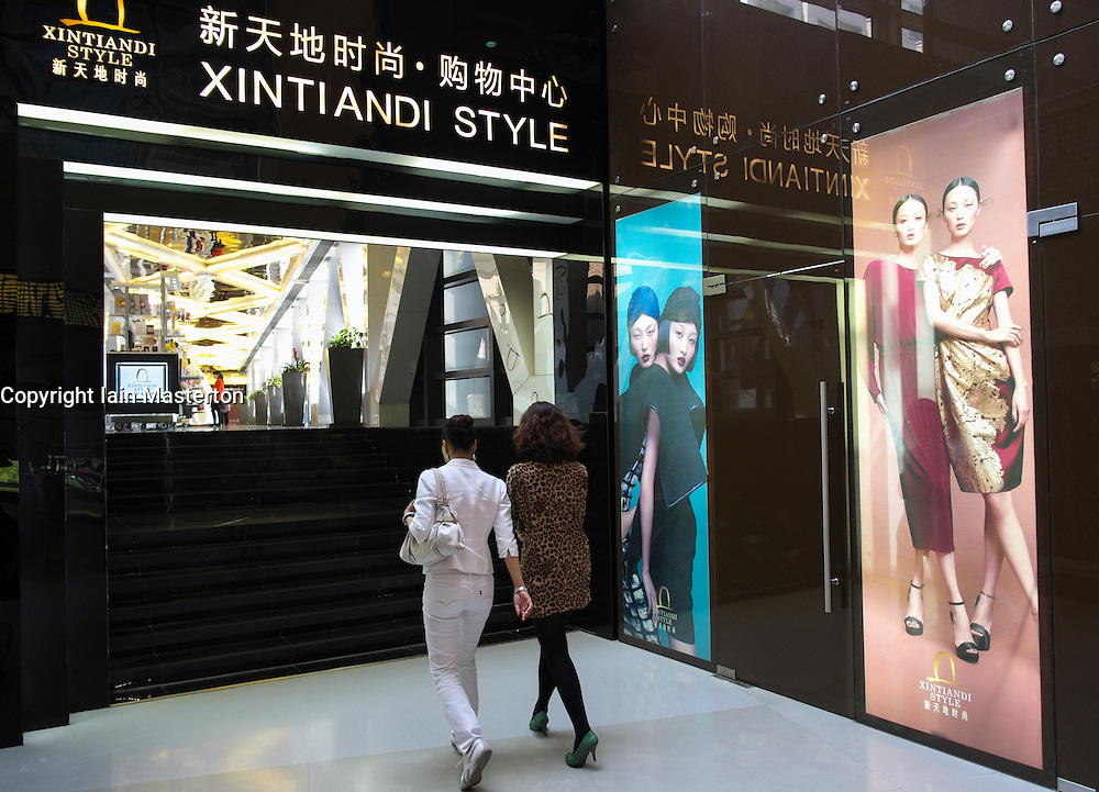 Two modern fashionable women walking in Xintiandi Style upmarket shopping mall in Shanghai