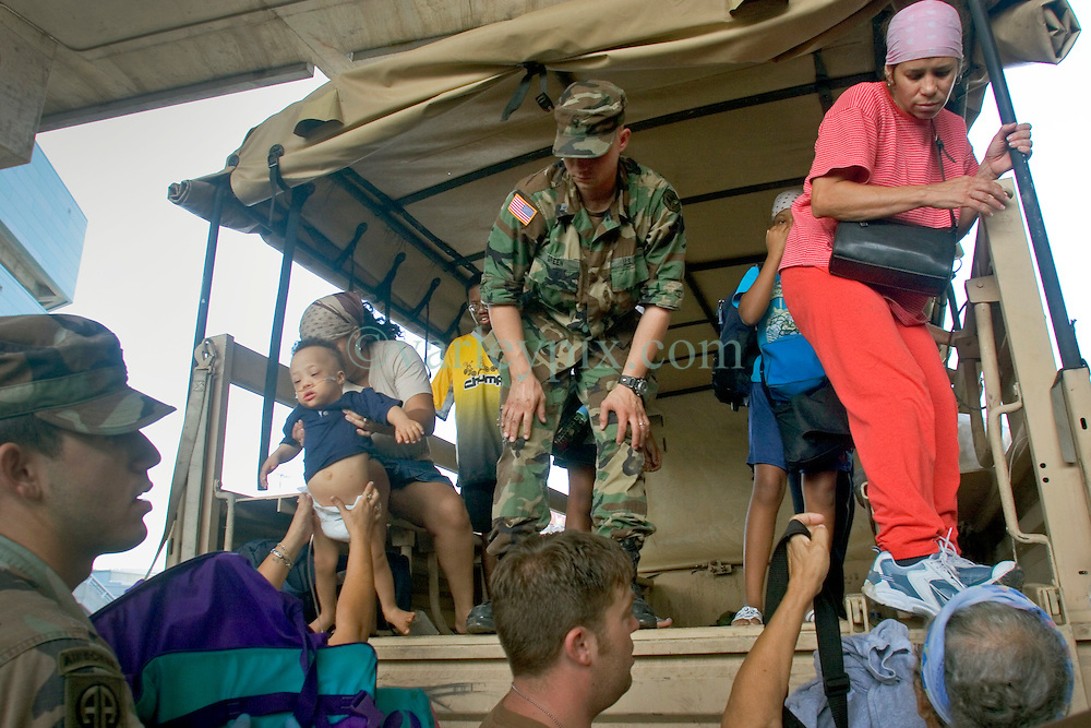 30 August, 2005. New Orleans Louisiana. Hurricane Katrina aftermath. <br /> Soldiers deliver storm evacuees to the makeshift hospital triage unit set up at the Superdome in New Orleans.<br /> Photo Credit: Charlie Varley/varleypix.com