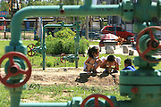Children play in the middle of CNPC oil pipes in a residential complex in Daqing, Heilongjiang province, China, on July 14, 2006. China National Petroleum Corp is the mother company of PetroChina. Photo by Servais Mont/Pictobank