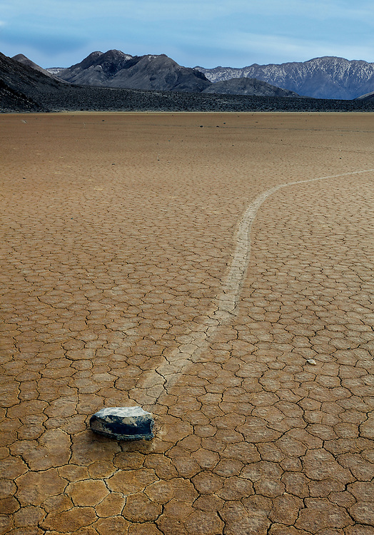 A roving rock on Racetrack Playa 5:00 PM. Floodwater makes the Racetrack basin slick. Strong winds push the rocks across the mud, leaving trails.