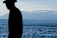 A loyal Aymara Indian man waits for a boat next to Lake Titicaca, Bolivia.