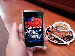 Reading e-book travel guide to Amsterdam with joint of cannabis in Abraxas coffeeshop in Amsterdam The Netherlands