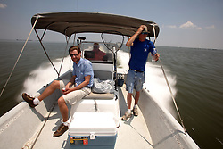 28 May 2010. Barataria Bay to Grand Isle, Jefferson/Lafourche Parish, Louisiana. <br /> Philip Sherwell of the Sunday Telegraph with Louisiana born and raised Justin Workmon (blue shirt) and Frank 'Peanut' Lensmeyer on the the eerily empty ocean where water that would ordinarily be crystal clear is now gravy coloured thanks to dispersed oil just off Grand Terre Island where Barataria Bay meets the Gulf of Mexico. Ordinarily the ocean would be filled with shrimp boats, sport fishermen, and sea birds, especially in the run up to memorial day weekend. The ecological and economic impact are devastating to the region. Oil from the Deepwater Horizon catastrophe is evading booms laid out to stop it thanks in part to the dispersants which means the oil travels at every depth of the Gulf and washes ashore wherever the current carries it. The Louisiana wetlands produce over 30% of America's seafood and are the most fertile of their kind in the world.<br /> Photo credit; Charlie Varley<br /> www.varleypix.com