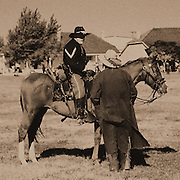 "Mounted member of 1800s living history frontier cavalry unit at Fort Concho in San Angelo, Texas produced in sepia tone. NOTE: Click ""Shopping Cart"" icon for available sizes and prices. If a ""Purchase this image"" screen opens, click arrow on it. Doing so does not constitute making a purchase. To purchase, additional steps are required."