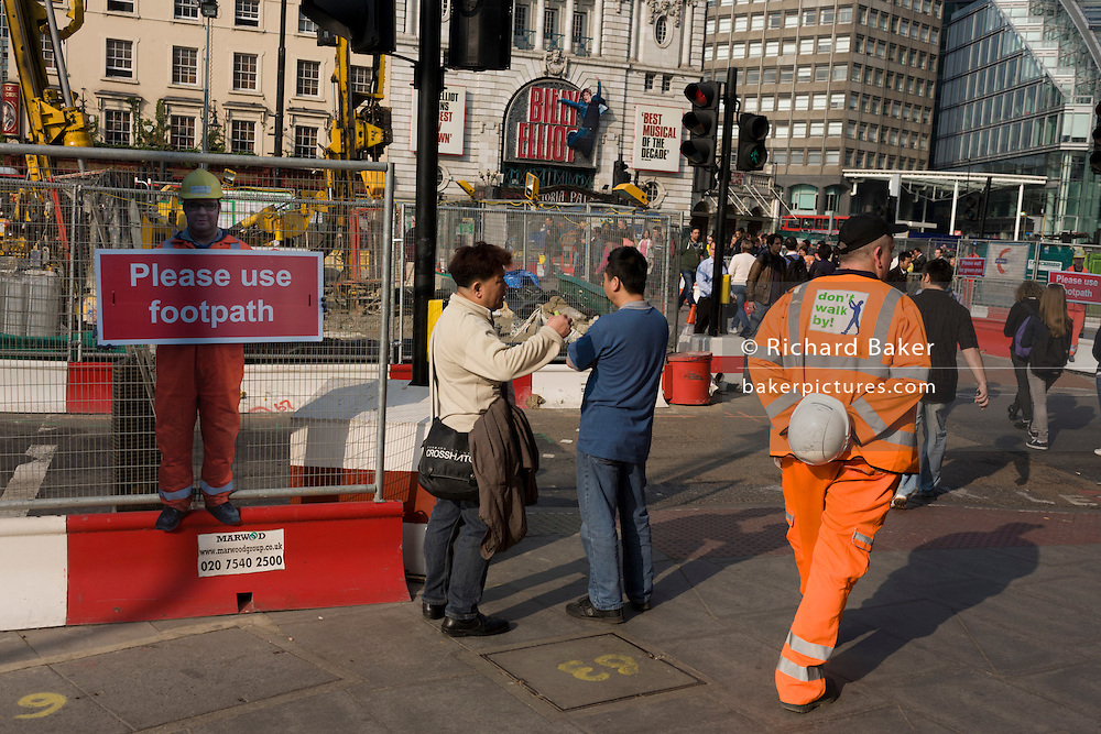 Real passing construction worker and a scaled human workman figure who warns pedestrians to stay on established footpath, and not wander into construction site roadways during street improvements in Victoria, central London.