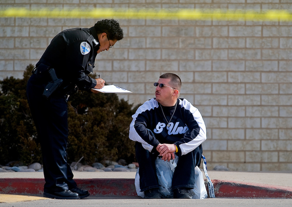 020509    Brian Leddy.A Gallup Police officer interviews Richard Mazone outside of Rio West Mall on Thursday afternoon. One of the people Mazone was with, Edward Lucero III, was grazed by a bullet during a shooting at the mall.