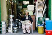 Pakistani retailer sits reading newspaper in village of Pattika, Pakistan