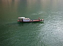 A traditional Chinese sampan makes its slow way under limited power on the Yangtze River in the vicinity of the Three Gorges Dam.