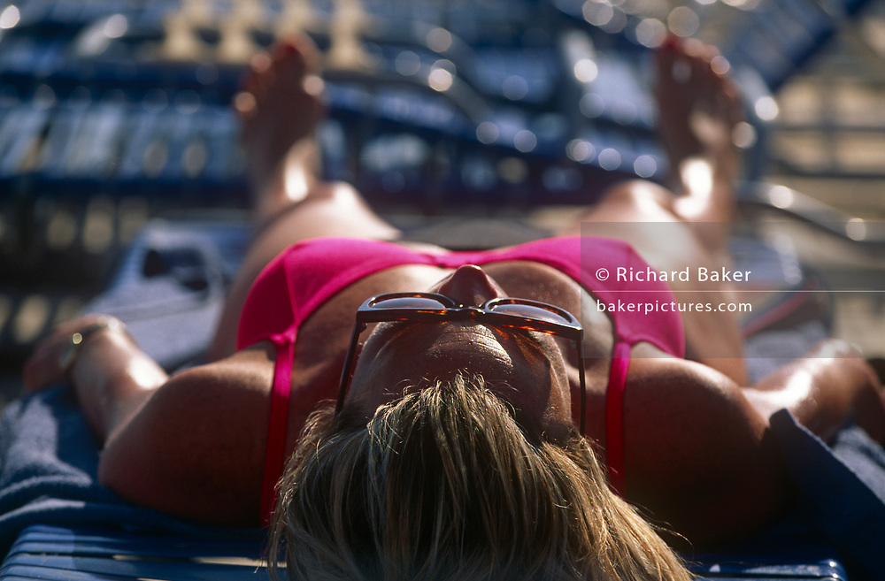 A lady wearing a bikini sunbathes on her vacation ship's upper deck on 15th May 1996, aboard the Carnival cruise ship Ecstasy, off the Gulf of Mexico, USA.