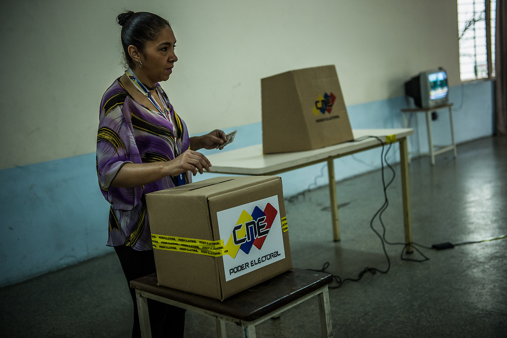"CARACAS, VENEZUELA - JULY 16, 2017: A few dozen government supporters participated in a rival vote, held right next to a plaza filled with thousands of people in line to vote in the ""Popular Consultation"" symbolic vote called for by the opposition. Maduro loyalists held a ""drill"" for the constituent assembly election, and the voting exercise was covered widely on state-run news outlets. The government prohibited TV and Radio stations to air coverage of the opposition's vote.  The government requires government employees to vote or risk being fired. They are also criticized for insinuating that people who benefit from government programs will lose their benefits if they do not vote for the ruling Socialist party. Many people say they continue to vote for them, out of fear.  PHOTO: Meridith Kohut"