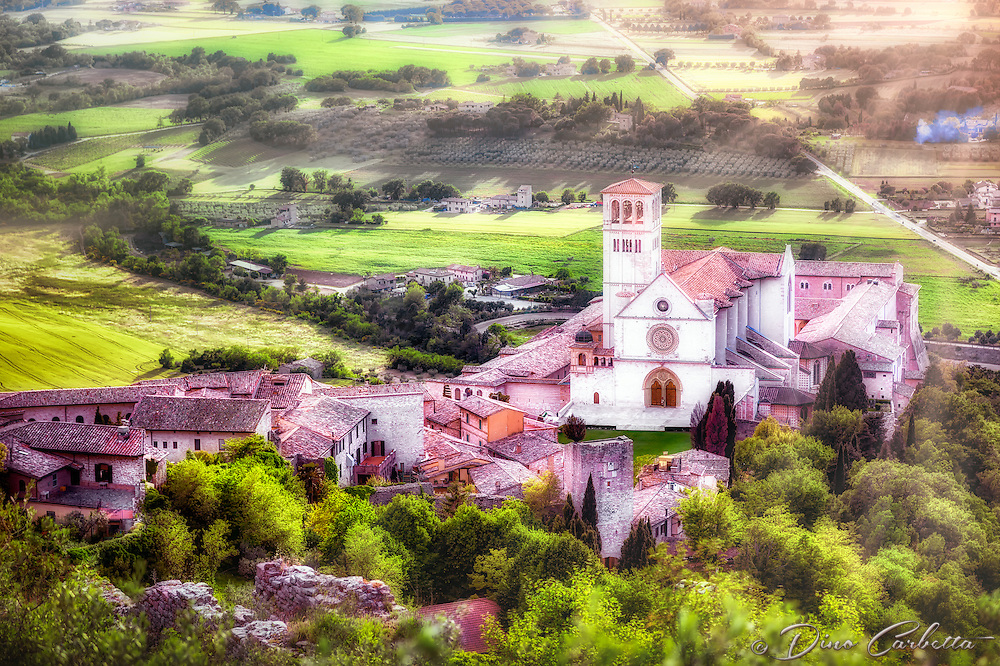 """""""Papal Basilica of St. Francis of Assisi, good evening!""""…<br /> <br /> This evening image was created while standing upon remnants of the fortress atop Assisi viewing down to the resting Basilica of Saint Francis. Upon arrival early that day I began taking photos the second I parked at Hotel Giotto just inside the walls in the foothills of Assisi. Perhaps Saint Francis arranged the dramatically perfect skies and coordinated every encounter. Beginning at the Basilica of Saint Francis, every second of the climb to the top of the mountain to the fortress Rocca Maggiore, a new surprise awaited around every corner. Upon my final steps to the top at almost sunset, the clouds parted and the low sun brightened as a slight mist of rain came down. Looking back over my shoulder, the appearance of a rainbow shone down between the Duomo of Saint Rufino, and the Basilica of Saint Clare. After the first small rainbow dissipated...I moved about 200 yards to the opposite view facing the setting sun over the Basilica of St. Francis. I was fortunate to capture several dramatic images just before another rainbow appeared behind me...a spectacular and blessed show by the hand of God.  This is one of the first images after gaining the top, right at the beginning of the heavenly skies erupting over the countryside."""