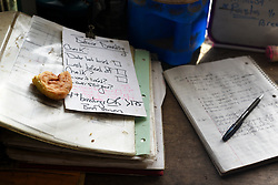 A half-eaten doughnut sits with a check list for breeding and a log of activity in the Green Acres barn while Craig Wortman does morning chores in South Randolph, Vt. Tuesday, January 5, 2016. (Valley News - James M. Patterson) Copyright Valley News. May not be reprinted or used online without permission. Send requests to permission@vnews.com.