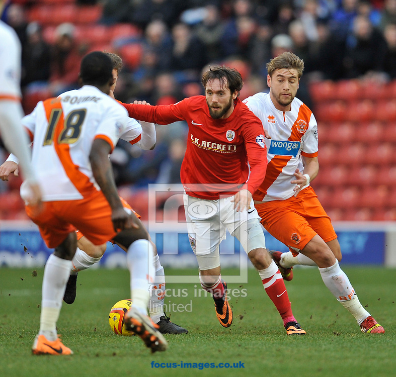 Picture by Richard Land/Focus Images Ltd +44 7713 507003<br /> 18/01/2014<br /> <br /> James O'Brien of Barnsley runs at Isaiah Osbourne of Blackpool during the Sky Bet Championship match at Oakwell, Barnsley.