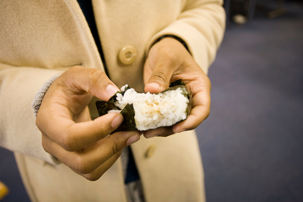 Waseda  University, Laura Woodland (white coat, i) age 20, San Diego; Japanese, Asian  Studies...eating onig,  a rice ball with different flavors inside like  Fish, cheese, fish eggs, umiboshi plum ect. wrapped with Nori a  crispy, salty seaweed paper like wrapping.