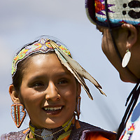 Native American woman smiling  with man in ceremonial clothing at Montana, Pow Wow