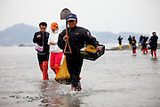 "Visitors on the slowly closing ""Mysterious Sea Road"" at Hoedong shore (Jindo island). Jindo is the 3rd biggest island in South Korea located in the South-West end of the country and famous for the ""Mysterious Sea Route"" or ""Moses Miracle"". Every spring thousands flock to the shores of Jindo to walk the mysterious route that stretches roughly three kilometers from Hoedong to the distant island of Modo. Materializing from the rise and fall of the tides, the divide can reach as wide as forty meters."