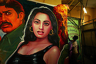 An assistant to Master painter Rehman, arranges hand made posters of Bollywood movies, now being replaced by machine made posters in Bombay, India Dec. 9, 2004. Rather than ripping down a poster once a film has stopped its run, Bombay's dwindling troupe of billboard painters simply cover their last masterpiece with the artwork for next week's big release.