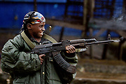 A 9(nine) year old Liberian government gunman fires down the 'Old Bridge' in rains during a lull in the battle for the bridges, Monrovia 28 July 2003. LURD(Liberians United for Reconciliation and Democracy) rebels drove government forces back over the bridge last night leaving the government forces on the Monrovia side of the bridge defending the city.This the Tenth day of continued fighting for the capital despite the call for ceasefire and heavy rains.<br /> EPA PHOTO/NIC BOTHMA