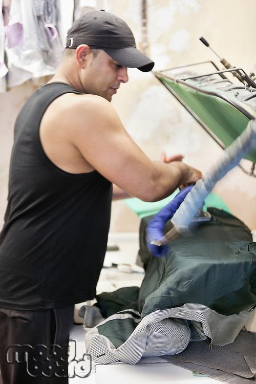Mature man ironing shirt in laundry