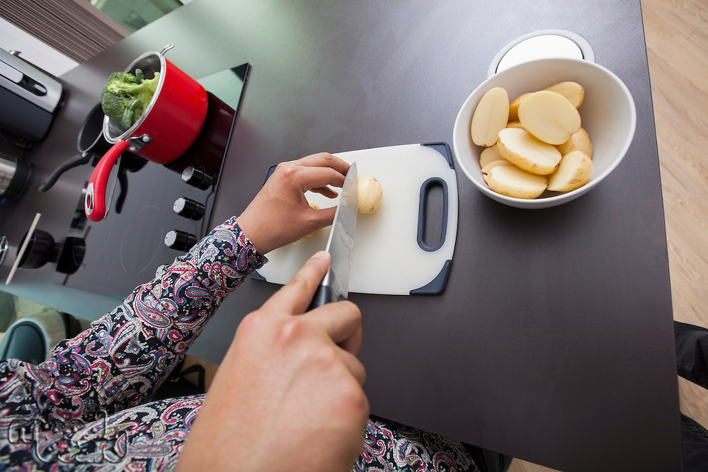 High angle view of man cutting potato at kitchen counter