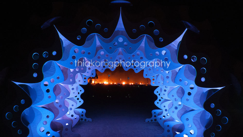 Looking out through a blue arch we see art burning in the distance, Burning Man 2012