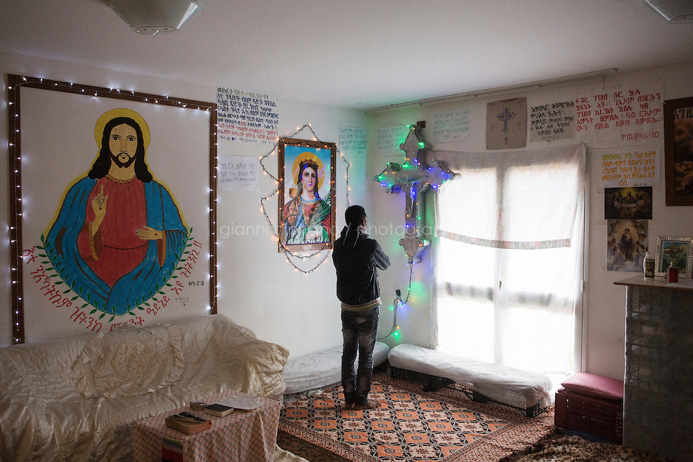 MINEO, ITALY - 26 NOVEMBER 2014: An Eritrean asylum seeker worhsips in an Eritrean Orthodox Tewahedo makeshift church in an apartment of the CARA (Accommodation Centre for Asylum Seekers) in Mineo where approximately 4,000 asylum seekers live, in Mineo, Italy, on November 26th 2014.<br /> <br /> By law, asylum-seekers can be held for 35 days in a CARA. In reality, the average stay is closer to a year.The Cara is located at the &quot;Residence degli Aranci&quot; (Residence of the Oranges), a small town built to accomodate the families of US soldiers operating at the Naval Air Station of Sigonella 40km away. Since 2011 the &quot;Residence degli Aranci&quot; hosts the Accommodation Center for Asylum Seekers, which has since then hosted more than 12,000 seekers of 47 nationalities and over 200 ethnic groups. The CARA of Mineo includes 404 houses. Each house hosts from 7 to 11 asylum seekers.