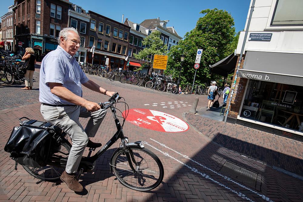 Een oudere man op een e-bike slaat af waar het voetgangersgebied begint. In Utrecht worden fietsers gewezen op een andere route. Vanaf 1 mei mogen fietsers gedurende het grootste deel van de dag niet meer door een deel van het centrum fietsen. Het voetgangersgebied is fors uitgebreid.<br /> <br /> A big painted sign on the road suggest cyclists another route to ride at the city center in Utrecht. A part of the center is closed for cyclists for the main part of the day.