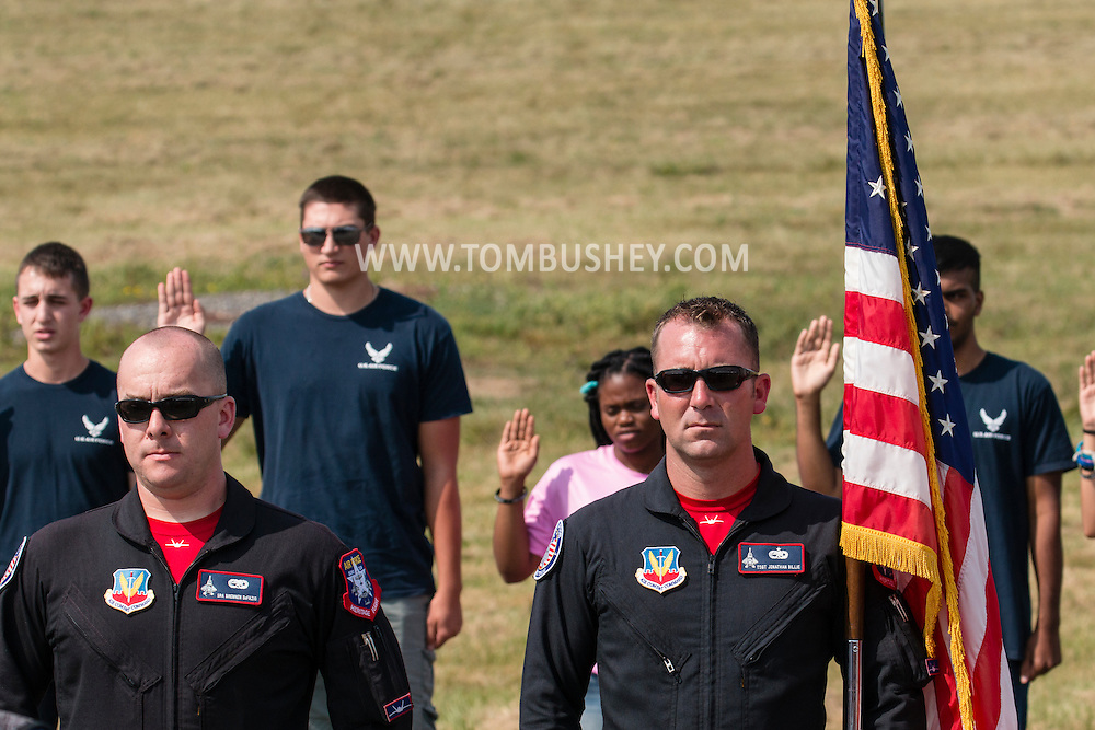 New Windsor, New York - Senior Airman Brennen DeFazio and Technical Sergeant Jonathan Billie of the United States Air Force's F-22 Raptor Aerial Demonstration stand at attention during an oath of enlistment ceremony on the first day of the New York Air Show at Stewart International Airport on Aug. 29, 2015.