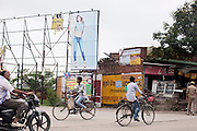 Villagers are passing by a billboard advertisement boasting a sexy model on heels, on a rural road outside of Varanasi, Uttar Pradesh, India.
