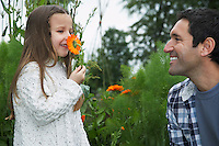 Girl (5-6) smelling flower with father outdoors
