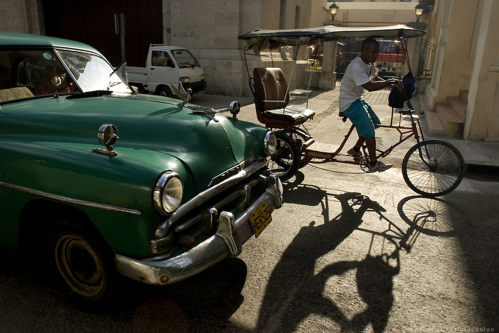 Tricycle taxi overtaking a car taxi in the traffic of Havana - CUBA