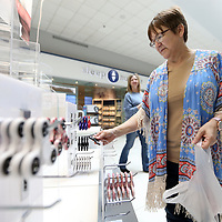 Judith Perrigo, an employee with Sunny Shades, stocks what Fidget Spinners she has left as they wait for a new shipment, at the Fidget Spinner kiosk booth inside the Mall at Barnes Crossing.