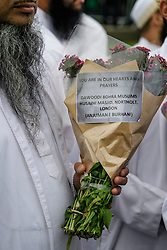 © Licensed to London News Pictures. 05/06/2017. London, UK. A muslim man holds flowers carrying a note at vigil at Potters Fields Park outside City Hall in London for those who lost their lives in the London Bridge terror attack. Three men attacked members of the public  after a white van rammed pedestrians on London Bridge. Ten people including the three suspected attackers were killed and 48 injured in the attack. Photo credit: Ben Cawthra/LNP