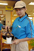 Waitress at Mister Donut chain pours an early morning cup of coffee for a guest in Ginowan City, Okinawa, Japan. (Supporting image from the project Hungry Planet: What the World Eats)