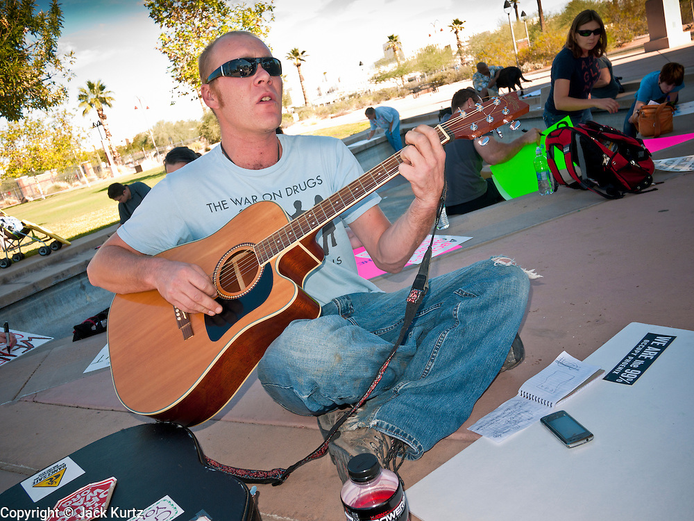"09 OCTOBER 2011 - PHOENIX, AZ: A man who identified himself as ""Dagger Pan"" plays guitar while people work on signs for the Occupy Phoenix sign painting party in Phoenix Sunday. About 50 people met in Steele Indian School Park in central Phoenix to paint signs for the Occupy Phoenix demonstration, which is expected to take place on Oct 15. Organizers are expecting more than 1,000 people to come downtown Saturday to protest against big banks and high unemployment.    PHOTO BY JACK KURTZ"