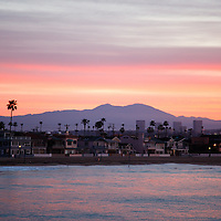 Photo of Newport Beach California sunrise over the Pacific Ocean shoreline looking east at Balboa Peninsula houses and mountains in Orange County Southern California.