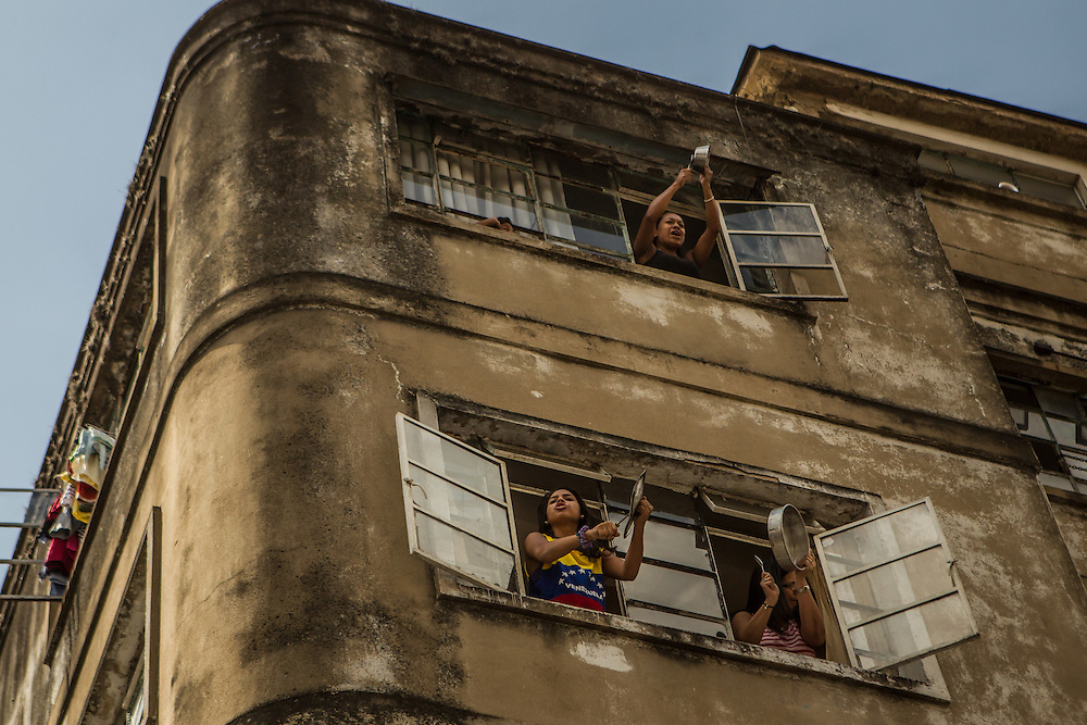 CARACAS, VENEZUELA - FEBRUARY 18, 2014:  Women bang pots and pans out their windows, a traditional form of protest in Venezuela, as an armored vehicle carrying Leopoldo Lopez, after he surrendered to the police, passes by their building. The government has said López is responsible for inciting recent street protests, that have killed three people. CREDIT: Meridith Kohut for The New York Times