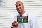 "Carlos Rosario at his home near Poughkeepsie, New York. He is holding tow photographs showing him and a fellow inmate working at 'his' garden at the Woodbourne Correctional Facility. He was released from prison in May 2010. ..Story: The Bard Prison Initiative.Former inmate Carlos Rosario, 35-year-old husband and father of four, was released from Woodbourne Correctional Facility after serving more than 12 years for armed robbery. Rosado is one of the students participating in the Bard Prison Initiative, a privately-funded program that offers inmates at five New York State prisons the opportunity to work toward a college degree from Bard College. The program, which is the brainchild of alumnus Max Kenner, is competitive, accepting only 15 new students at each facility every other year. .Carlos Rosario received the Bachelor of Arts degree in social studies from the prestigious College Saturday, just a few days after his release. He had been working on it for the last six years. His senior thesis was titled ""The Diet of Punishment: Prison Food and Penal Practice in the Post-Rehabilitative Era,"".Rosado is credited with developing a garden in one of the few green spaces inside the otherwise cement-heavy prison. In the two years since the garden's foundation, it has provided some of the only access the prison's 800 inmates have to fresh vegetables and fruit...Rosario now works for a recycling company in Poughkeepsie, N.Y...Photo © Stefan Falke"
