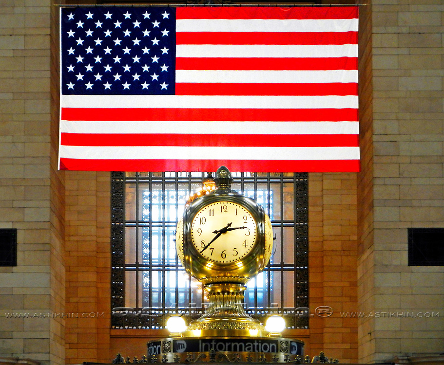 American flag and Big illuminated clock at Grand Central Terminal Station, New York City.