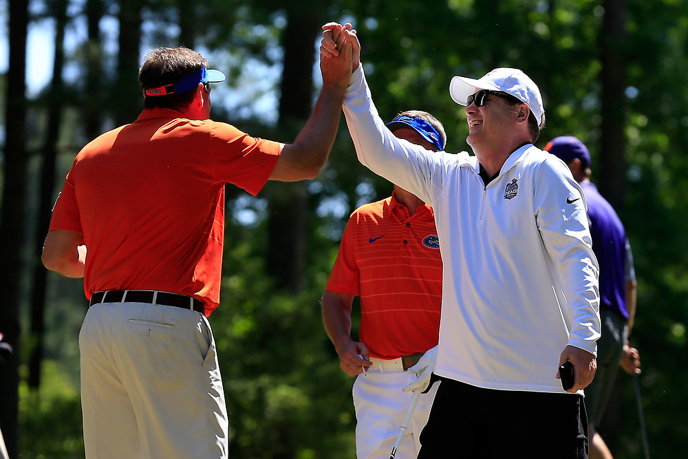Dan Mullen high fives Gary Stokan after getting pranked with an exploding golf ball during the Chick-fil-A Peach Bowl Challenge at the Oconee Golf Course at Reynolds Plantation, Sunday, May 1, 2018, in Greensboro, Georgia. (Paul Abell via Abell Images for Chick-fil-A Peach Bowl Challenge)