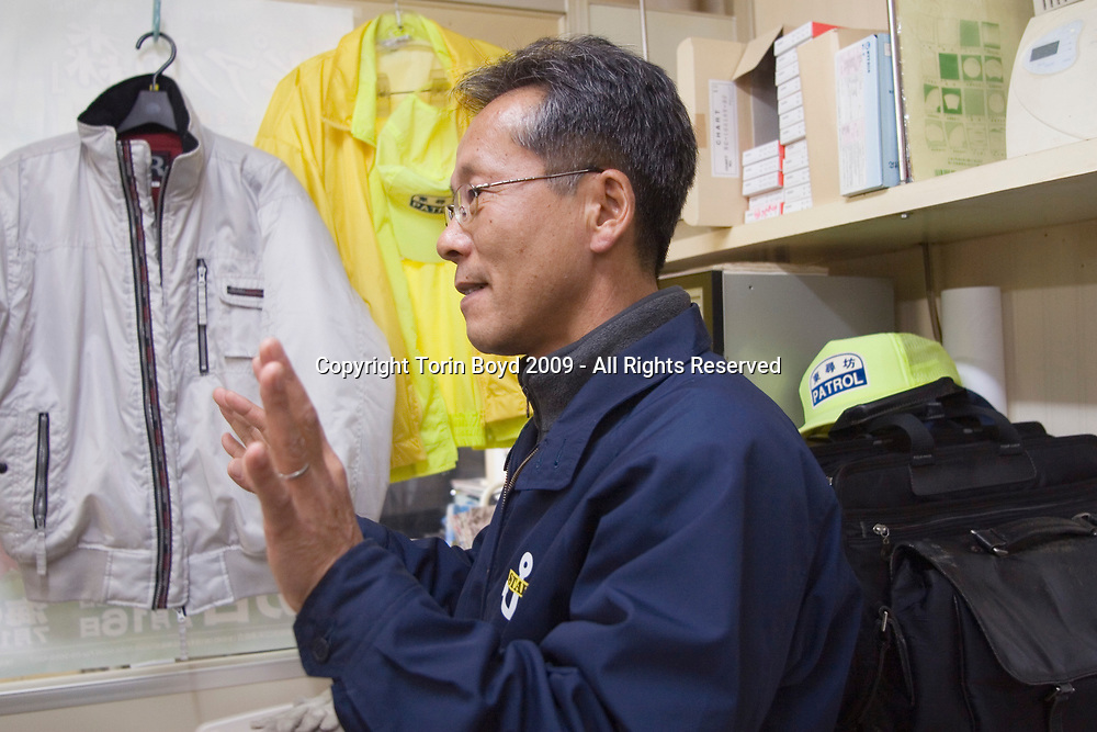 Nov. 26, 2009, Sakai City, Japan: This is Satoru Kobari, President of the Tojinbo Kankou Kyokai, the tourism association that promotes the majority of tourism for Tojinbo, a popular tourist attraction on the Japan Sea coast. He is in his office just above the cliffs of Tojinbo on Nov. 26, 2009 where he also operates boat cruises of the area. However Tojinbo is also known for the number of suicide deaths that occur here annually and Kobari and his collegues are somewhat unsettled by the efforts of an NPO called Kokoro ni Hibiku Bunshu Henshukyoku, which patrols the Tojinbo cliffs to prevent suicide attempts. This NPO headed by by retired policeman Yukio Shige, who along with a group of volunteers patrols the cliffs daliy to deter those contemplating jumping to their deaths. However many merchants at Tojinbo feel Mr. Shige and his NPO is tarnishing the image of Tonjinbo due to much unwanted publicity and attention. According to Shige, age 65, of Fukui Prefecture, in the past five years since he founded his NPO he is responsible for talking 222 people out of killing themselves. But even with Shige's efforts, the deaths here continue and as of late November, 2009, the current number of annual suicides at Tojinbo stands at thirteen. Japan has one of the highest suicide rates in the world and 2009 may surpass the record 34,427 deaths that occurred here in 2003. This increase is though to be a result of the Japanese recession which has been worsened by the global economic downturn. Depression is the number one cause for suicide in Japan, followed by illness and debt. Photo by Torin Boyd.