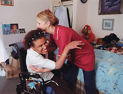 Care manager in residential care centre helping young woman with Cerebral Palsy transfer from bed into wheelchair,