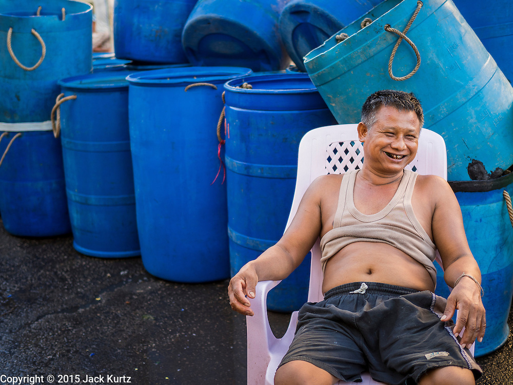 """11 JUNE 2015 - MAHACHAI, SAMUT SAKHON, THAILAND:  A Burmese migrant laborer relaxes during a break at the Talay Thai market in Mahachai. Labor activists say there are about 200,000 migrant workers from Myanmar (Burma) employed in the fishing and seafood industry in Mahachai, a fishing port about an hour southwest of Bangkok. Since 2014, Thailand has been a Tier 3 country on the US Department of State Trafficking in Persons Report (TIPS). Tier 3 is the worst ranking, being a Tier 3 country on the list can lead to sanctions. Tier 3 countries are """"Countries whose governments do not fully comply with the minimum standards and are not making significant efforts to do so."""" After being placed on the Tier 3 list, the Thai government cracked down on human trafficking and has taken steps to improve its ranking on the list. The 2015 TIPS report should be released in about two weeks. Thailand is hoping that its efforts will get it removed from Tier 3 status and promoted to Tier 2 status.       PHOTO BY JACK KURTZ"""